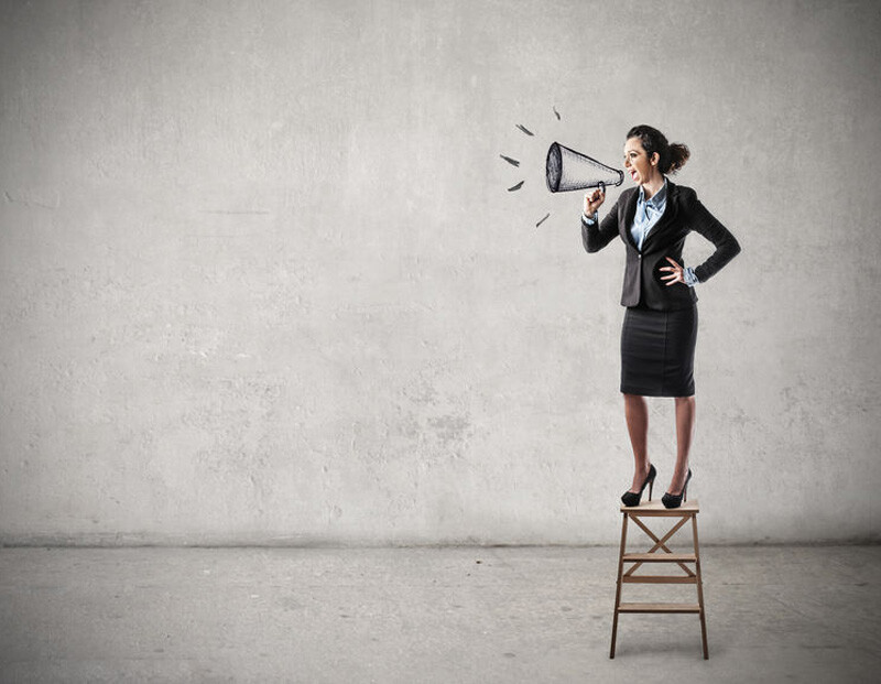 A woman stands on a stepladder and shouts into a cartoon-drawn megaphone